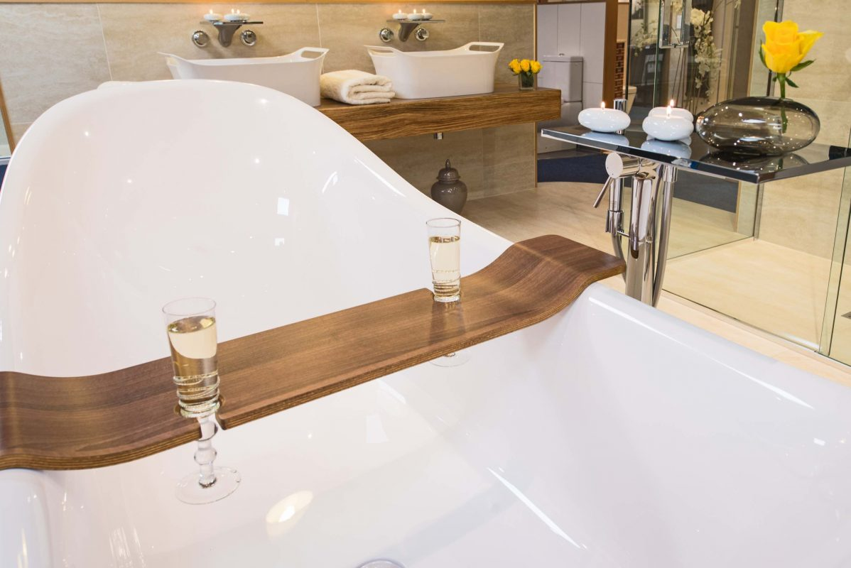 A ceramic bath with a wooden drinks holder