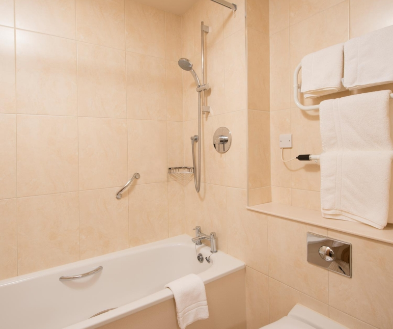 An accessible bathroom with hand rails incorporated in the bath and shower facility