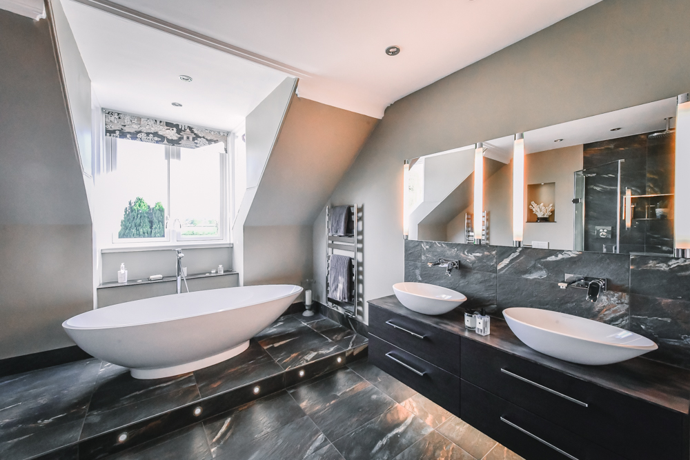 A black marble tiled bathroom with an oval free standing ceramic bath