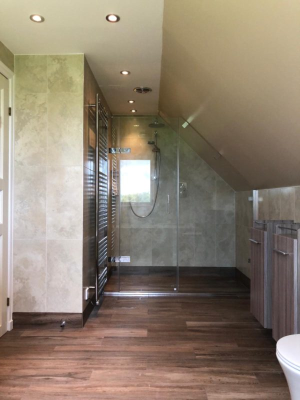 A completed bathroom, with open planned shower and sloping roof.